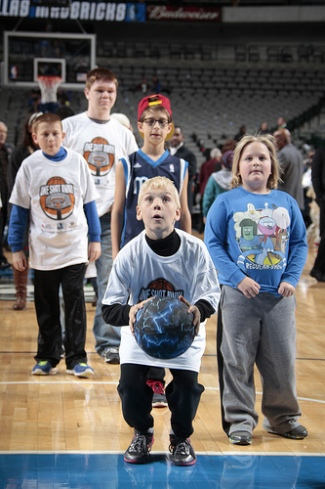 """Children making a shot on the basketball court after the Mavericks game during the """"One Shot Away"""" event."""